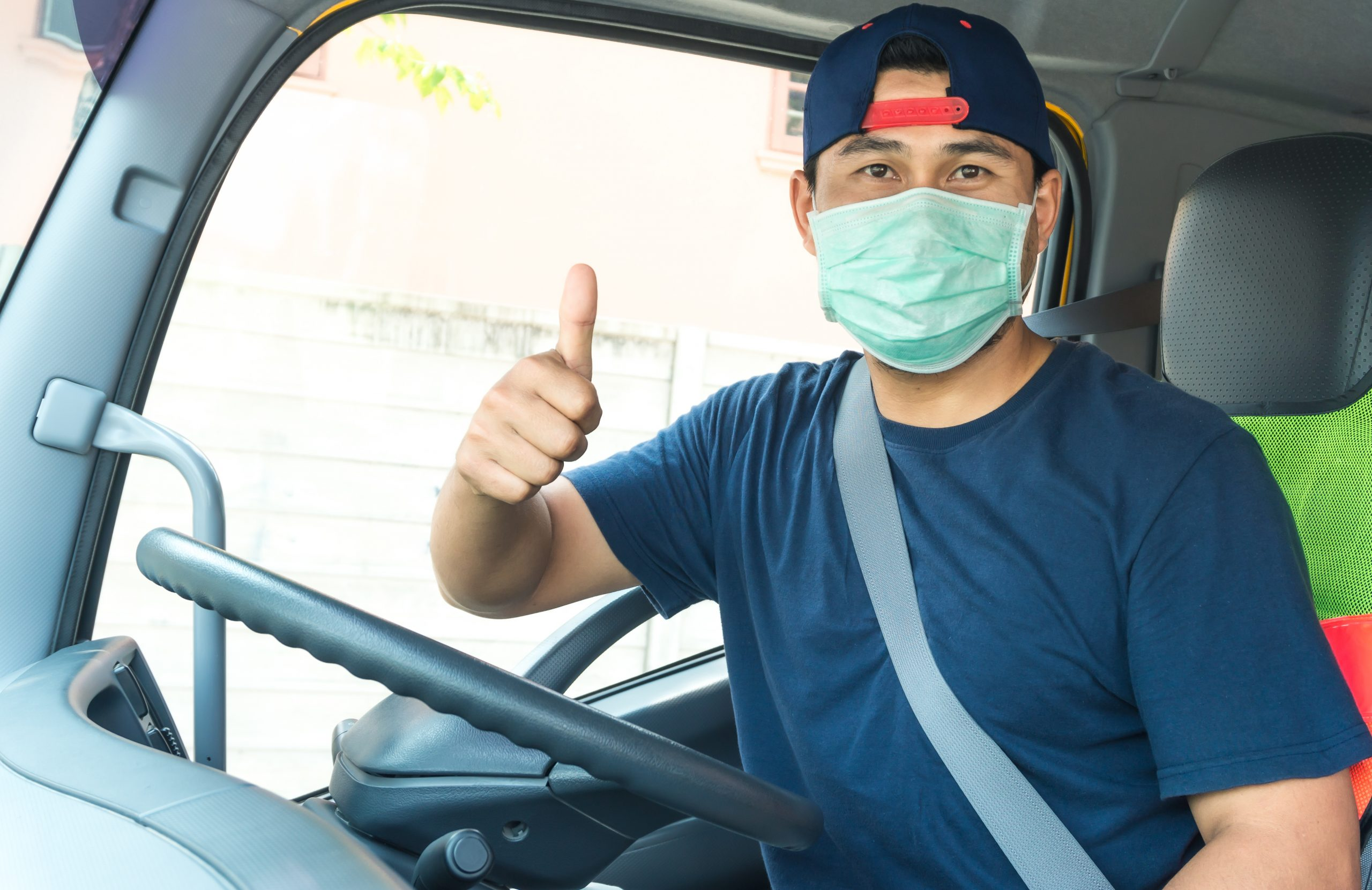 Truck driver with mask giving a thumbs up